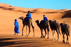 Un Tuareg e i suoi bambini attraversano l'area di Erg Chebbi nel deserto del Sahara (foto Martin Harvey / Alamy / Milestone Media)
